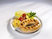 Two grilled sausages with potato and tomato salad
