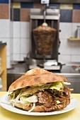 Ein Döner Kebab mit Fleischspiess im Hintergrund