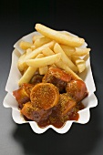 Currywurst with chips in paper dish
