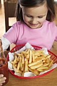 Small girl sitting in front of a basket of chips, ketchup
