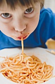 Small boy eating spaghetti