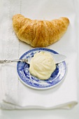 Croissant, butter on plate