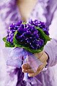 Hand holding a posy of violets
