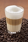 A glass of latte macchiato on a heap of coffee beans