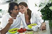 Man feeding woman a spoonful of muesli