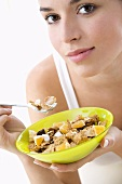 Young woman eating cornflakes with fruit and yoghurt