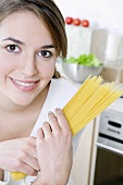 Woman holding a bundle of spaghetti in her hands