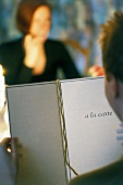 Man reading menu in restaurant with woman in background