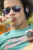 Jugendlicher trinkt Bier und hört Musik