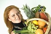 Junge Frau hält Einkaufskorb mit frischen Lebensmitteln