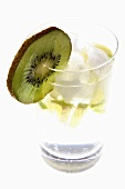 Mineral water with lime wedges, ice cubes and kiwi fruit