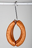 Four red bratwurst on a hook