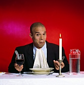 Man sitting in front of empty plate with water and wine