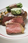 Beef steak with herb butter and bacon-wrapped beans