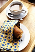 A cup of coffee with a chocolate croissant on a tray