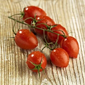 Plum tomatoes on the vine on wooden background