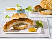 Two bread rolls filled with sausages on paper plates