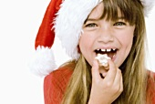 Girl in Father Christmas hat eating a cinnamon star