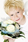 Blond boy holding bouquet of white roses in his hands