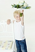 Blond boy with bouquet of white roses