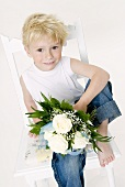 Boy with bouquet of white roses sitting on a chair