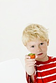 Blond boy holding a strawberry in his hand