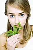 Young woman smelling fresh basil