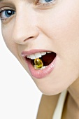 Woman with vitamin capsule between her teeth