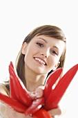 Junge Frau hält rote Peperoni mit ausgestreckten Armen