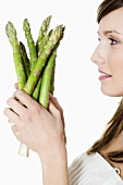 Young woman holding green asparagus in her hands