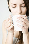 Young woman drinking out of a cup