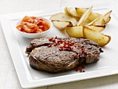 Ribeye steak with baked potato wedges