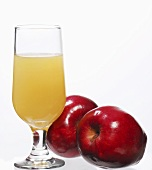 A glass of apple juice with two red apples