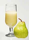 A glass of pear juice with a pear