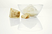 A piece of Parmesan and grated Parmesan in glass bowl