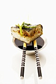 Sushi on chopsticks on a small bowl of soy sauce