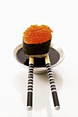 Gunkan maki on chopsticks on small bowl of soy sauce