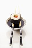 Futo maki with chopsticks and soy sauce