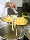Putting tagliatelle into a frying pan