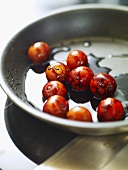 Frying cocktail tomatoes with balsamic vinegar in frying pan