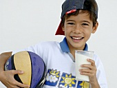 Boy holding a glass of milk and a ball