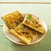 Three pieces of onion tart on a plate
