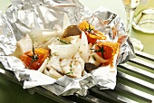 Halibut in aluminium foil with tomatoes and mushrooms