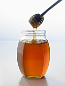 Honey running from honey dipper into jar