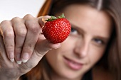 Young woman holding a strawberry in her hand