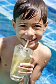 Boy drinking a glass of iced tea in pool