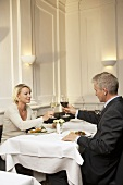 Married couple raising glasses of wine during a meal