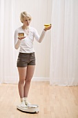 Young woman with a piece of cake and bananas on scales