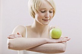Young woman balancing an apple on folded arms