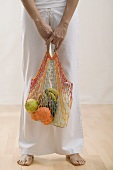 Young woman with string bag full of groceries